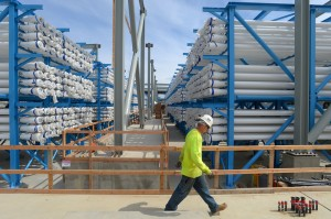 A worker walks by racks containing the reverse osmosis cartridges at the  billion Carlsbad desalination plant in Carlsbad, CA on Monday, May 5, 2014. When completed in 2016, it will be the largest desalination plant in the western hemisphere and will produce 50 million gallons per day and will supplement the regional water supply.  (Photo by Scott Varley/Media News Group)