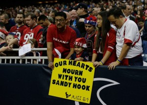 HOUSTON, TX - DECEMBER 16: Houston Texans fans take a moment to remember the victims of a massacre at Sandy Hook Elementary School in Newtown, Connecticut prior to the start of the game against the Indianapolis Colts at at Reliant Stadium on December 16, 2012 in Houston, Texas. (Photo by Scott Halleran/Getty Images)